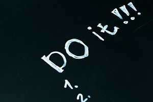 inscription do it list drawn with chalk on a school blackboard dark