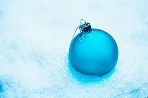 Round Blue Christmas balls on the snow new cold