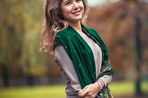 Portrait of a young girl with  green scarf on the background  autumn park