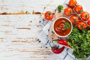 Ketchup and ingredients on wood background
