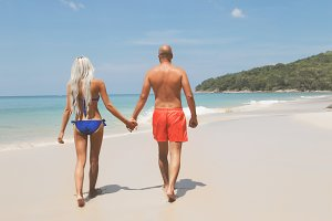 Pretty couple walking on a tropic beach