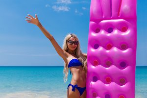Slim blonde woman with air mattress tropic beach