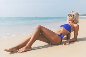 Slim blonde long haired woman in bikini on beach