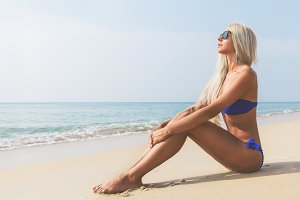 Slim blonde long haired woman in bikini on beach