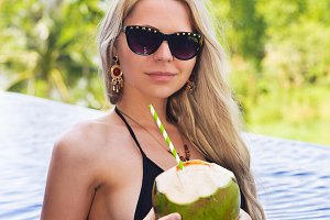 blonde woman in sunglasses with detox coconut