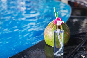 Coconut juice drink with flower and bottle of oil