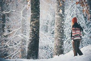 Woman walking alone in winter forest