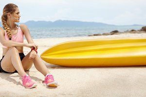Beautiful blonde girl with athletic body relaxing after long run, spending vacation in tropical country. Female jogger in sportswear sitting on beach near yellow boat against blue sea background