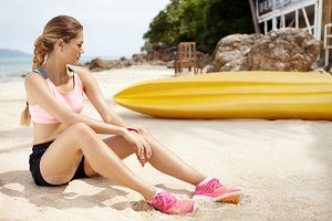 Tired woman runner in pink sneakers relaxing after acive workout, sitting on beach near yellow boat. Female athlete resting near bungalow on rocky coast against green jungle and blue sea background