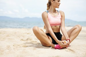 Sports, fitness and healthy lifestyle. Fit woman runner looking concentrated while stretching legs by sea, doing butterfly stretch, sitting on beach sand with hands on top of her feet before jogging