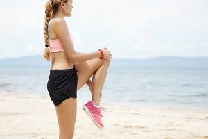 Side portrait of attractive sporty woman with long braid stretching on beach against blue sea background. Blonde female jogger in sportswear warming up her legs before morning run at the ocean