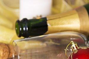 Bottle of champagne and glass with Christmas decorations