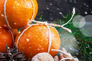 Christmas composition with tangerines, cinnamon and walnuts, snowing