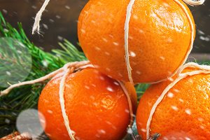 Tangerines and fir-cone as the Christmas Decor, snowing.