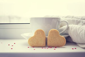 Two biscuits in the shape of a heart on a background with a cup