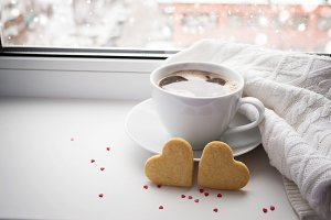Two sponge heart and a cup of hot coffee on the window