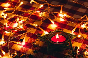 candle and garland lights in the background of a checkered tablecloth