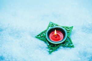 red candle in green candlestick star on the snow