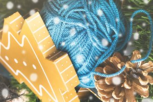 Gift box with woolen winter clew on green branches. Snow