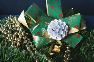 Dark background with baubles, green branch and gift bow