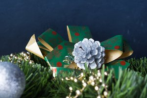 Black background with baubles, green branch and gift bow