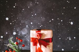Christmas gift on a wooden table. Christmas toy. Christmas composition. Christmas concept. Snowflakes. Gray background.