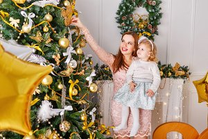 Mother and daughter. Christmas tree