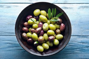 Wooden bowl full of olives
