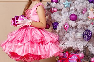 Girl with gift near Christmas tree