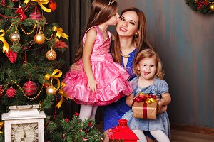 Daughter kissing mother. Christmas