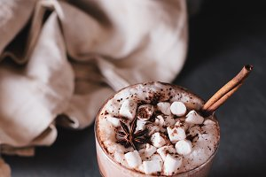 Cocoa or latte or hot chocolate with marshmallow and flavored with cinnamon. On a gray concrete background. Christmas present. Christmas concept. Christmas holiday.
