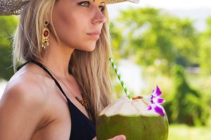 blonde woman in straw hat with detox coconut