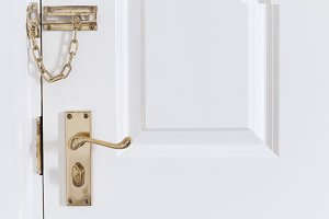handle and chain on the white front door