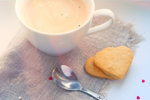 Cup of coffee, cookies, hearts and rays of light. Valentine's Da