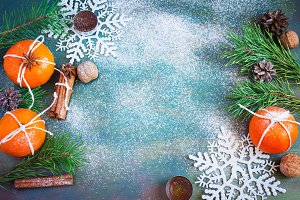 Winter Christmas decorations - tangerines, walnuts, snowflakes, cinnamon and candles. with space for text
