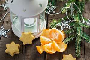 Mandarin, lantern, tree branches, homemade cookies on a wooden b