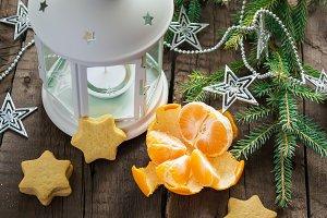 Mandarin, lantern, tree branches, homemade cookies on a wooden b