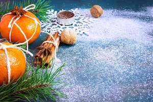 Mandarins as a Christmas decoration, fir branches and cinnamon on a snowy blue background. with space for text