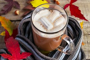 Hot cocoa marshmallow  on a knitted woolen scarf. Warming drink