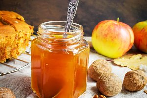 Honey in a glass jar, walnuts and apples