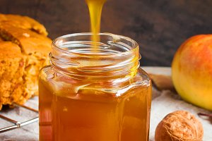 Honey dripping from a spoon in a jar in the autumn background