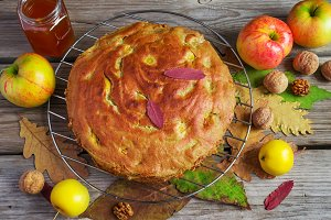 Apple pie with honey and walnuts, autumn still life, style rustic