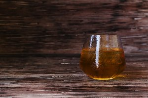glass of whiskey with ice on rustic wooden table