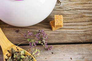 Dry herb tea in a wooden spoon and white teapot