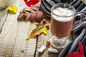 Cocoa with marshmallows, scarf and autumn leaves, with space for