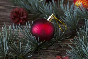 Christmas balls with fir branches lying on a wooden table