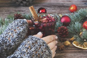 woman's hands holding a cup of mulled wine between