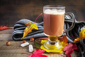 Autumn still life with hot cocoa, cozy scarf and autumn leaves