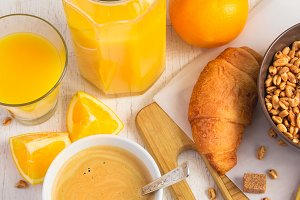 Breakfast concept - orange juice, croissant and coffee on a whit