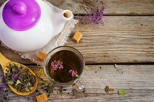 White teapot, dry herbal tea, cup and brown sugar